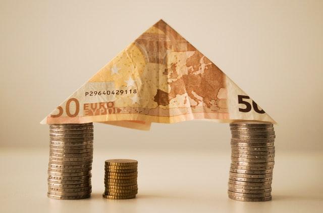 Dach domu z banknotu podtrzymywany przez monety